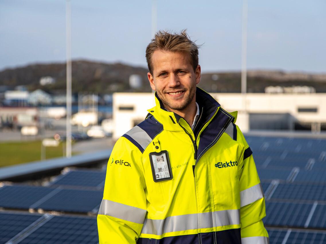 Prosjektleder Daniel Mathisen med solcellepaneler i bakgrunnen.