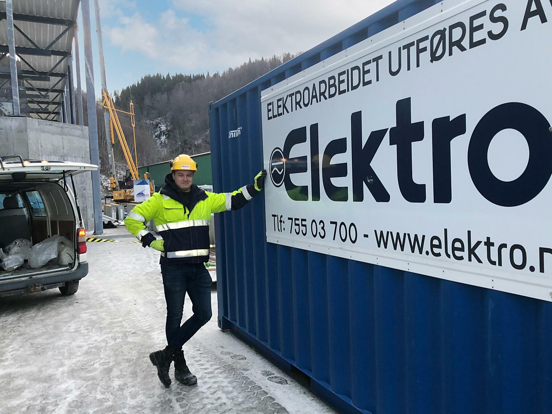 Mann i arbeidtøy lener seg på kontainer dekorert med