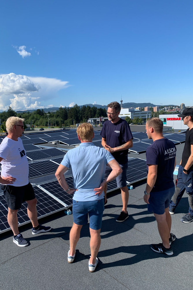 Fem personer står på tak og ser på solcelleanlegg.